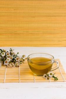 Chá de camomila brewed forte em uma tigela de vidro transparente em uma esteira de bambu na mesa de madeira branca