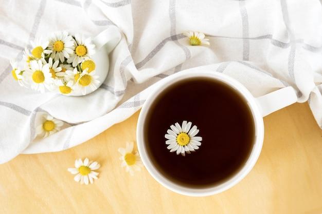 Chá de camomila com toalha de cozinha e camomila em copo branco sobre a mesa de madeira. chá erbal com camomila. vista superior. plano leigo.