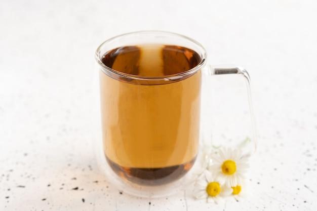 Chá de camomila e camomila em caneca de vidro na mesa de cimento branco. chá de ervas. vista do topo. postura plana.
