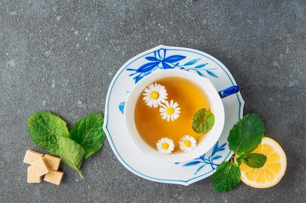 Chá de camomila em uma xícara e pires com limão, cubos de açúcar mascavo e folhas verdes, vista superior, sobre um fundo cinza de estuque
