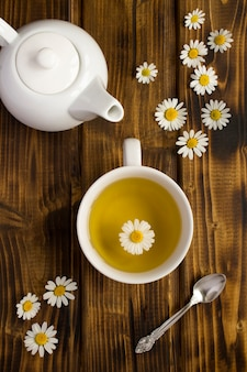 Chá de camomila na xícara branca e bule no fundo de madeira. vista do topo. fechar-se.