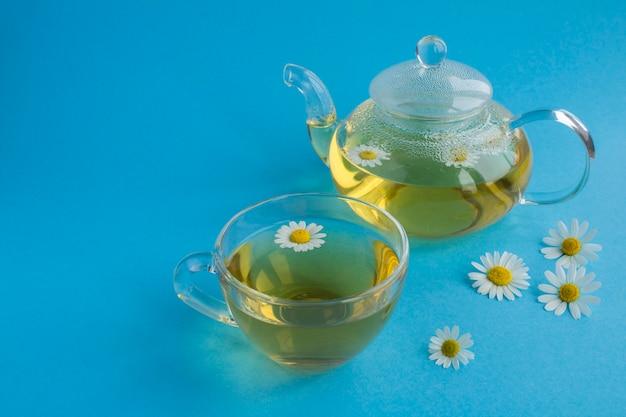 Chá de camomila no bule de amd copo de vidro no fundo azul. fechar-se. copie o espaço.