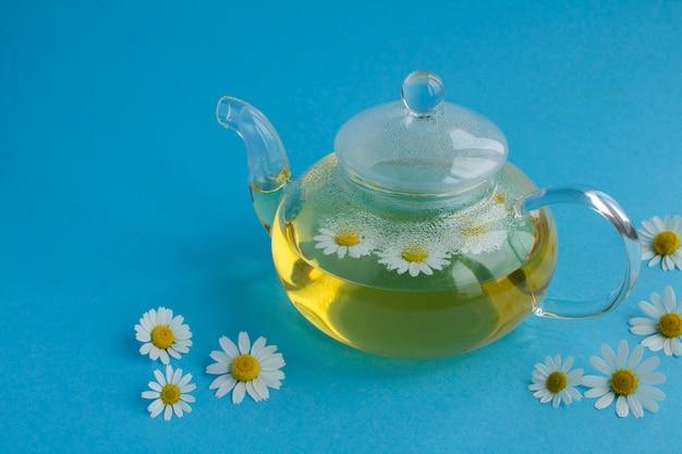 Chá de camomila no bule de vidro sobre o fundo azul. fechar-se. copie o espaço.