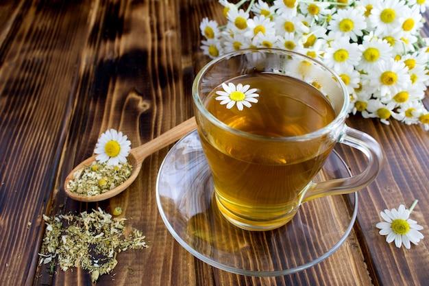 Chá de camomila no copo de vidro sobre a mesa