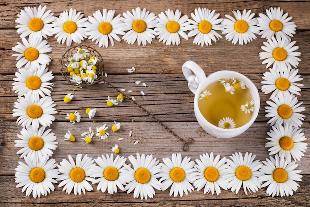 Chá de camomila no fundo de madeira. em um quadro de flor