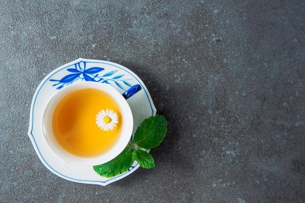Chá de camomila orgânica em uma xícara e pires com folhas verdes vista superior sobre um fundo cinza estuque