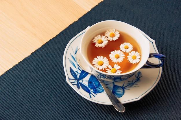 Chá de camomila perfumado em uma xícara e molho em um tapete escuro e fundo de mesa de madeira. vista de alto ângulo.