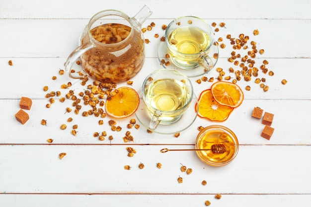 Chá de camomila saudável no copo de vidro. bule, pequeno pote de mel