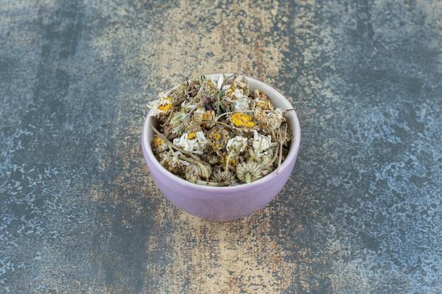 Chá de camomila seco em uma tigela roxa.