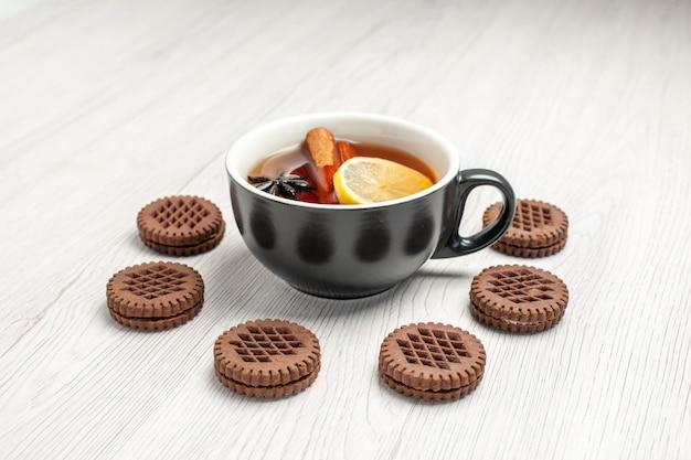 Chá de canela com limão e vista frontal arredondado com biscoitos no fundo branco de madeira