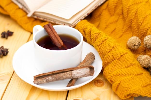 Chá de canela quente aromático coberto com um lenço quente em um fundo de madeira de outono. confortável lendo um livro.