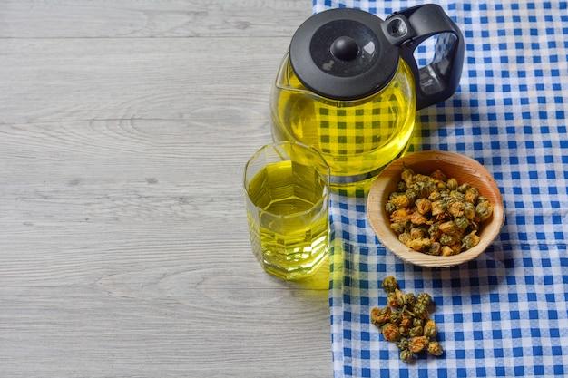Chá de crisântemo com chá de crisântemo seco em uma tigela de madeira em cima da mesa