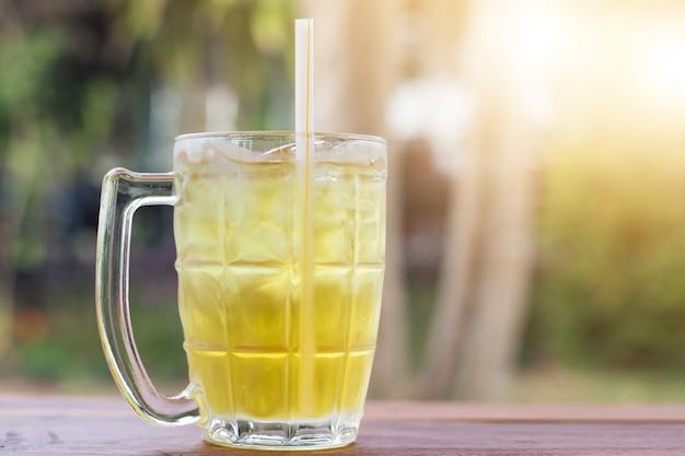Chá de crisântemo gelado na vista lateral de mesa de madeira com fundo verde porta natural durante a hora do dia no verão