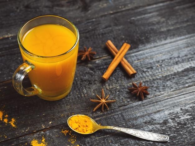Chá de cúrcuma em uma xícara de canela em um fundo escuro de madeira