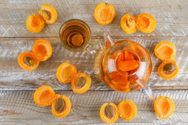 Chá de damasco com damascos no bule e caneca de vidro na mesa de madeira, plana leigos.