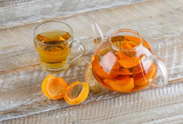 Chá de damasco em caneca de vidro e bule com damascos vista superior em uma mesa de madeira