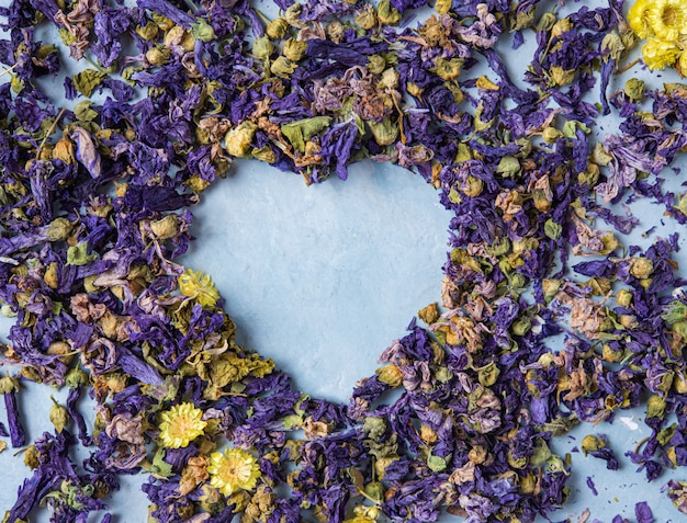 Chá de ervas aromáticas lavanda e camomila coração solto na macro de mesa de madeira azul