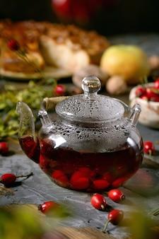 Chá de ervas com bagas de roseira brava em bule de vidro
