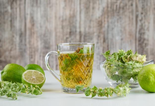 Chá de ervas com ervas, limão em um copo de vidro em branco e sujo,