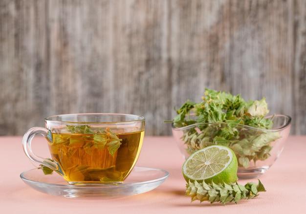 Chá de ervas com ervas, limão em um copo de vidro em rosa e madeira,
