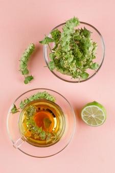 Chá de ervas com ervas, limão em um copo de vidro na rosa, vista superior.