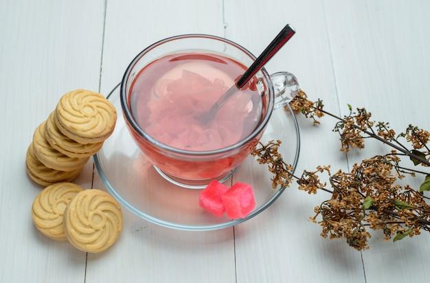 Chá de ervas com ervas secas, biscoitos, cubos de açúcar, colher em um copo na superfície de madeira, vista de alto ângulo.