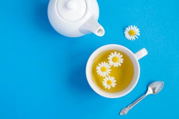 Chá de ervas com flor de camomila na xícara branca e bule no fundo azul. vista do topo. copie o espaço.