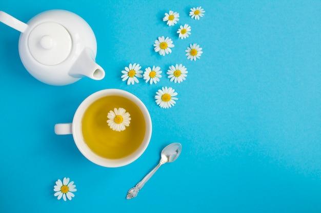 Chá de ervas com flor de camomila na xícara branca e bule. vista do topo. copie o espaço.