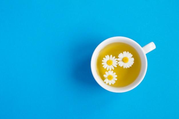 Chá de ervas com flor de camomila na xícara branca sobre fundo azul. vista do topo. copie o espaço.