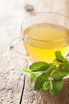 Chá de ervas com folhas verdes em copo de vidro