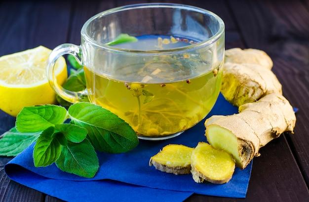 Chá de ervas com hortelã e gengibre em uma mesa de madeira