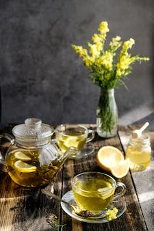Chá de ervas com limão e mel em copo de vidro e bule