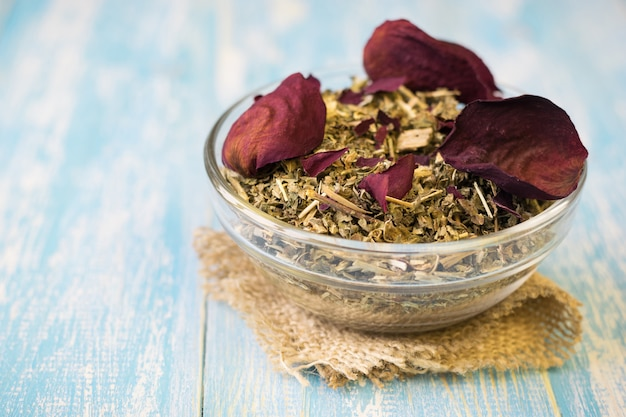 Chá de ervas com pétalas de rosa em uma mesa rústica. beba medicina alternativa.