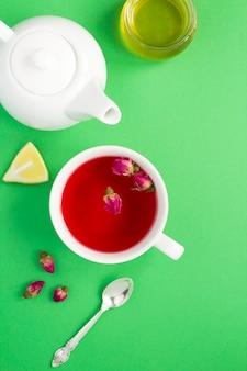 Chá de ervas com rosas cor de rosa na xícara branca na mesa verde. vista do topo. copie o espaço.