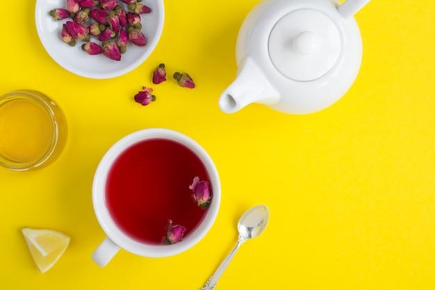 Chá de ervas com rosas cor de rosa no copo branco no amarelo