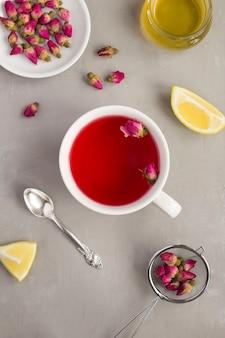 Chá de ervas com rosas rosa na xícara