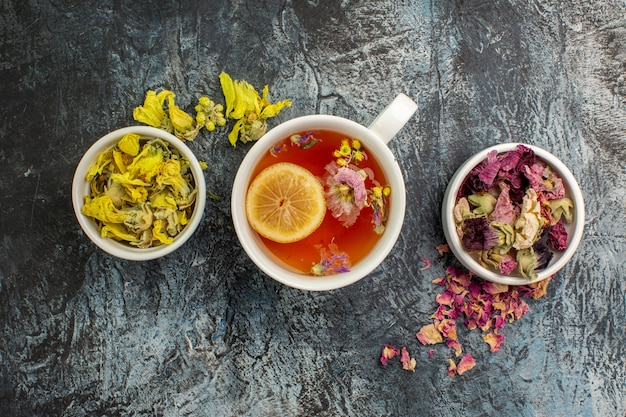 Chá de ervas com tigelas de flores secas em cinza
