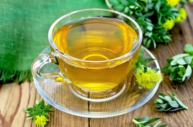 Chá de ervas curativas em copo de vidro com flores rhodiola rosea, pano verde em uma placa de madeira