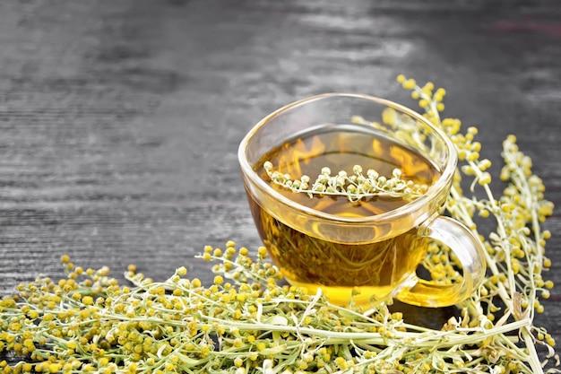Chá de ervas de absinto cinza em um copo de vidro, flores frescas de artemísia no fundo escuro da placa de madeira