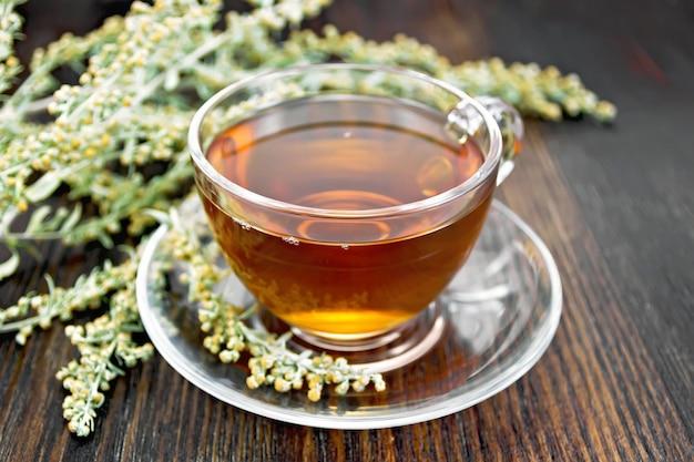 Chá de ervas de absinto em um copo de vidro em um pires, raminho de artemísia cinza no fundo de tábuas de madeira