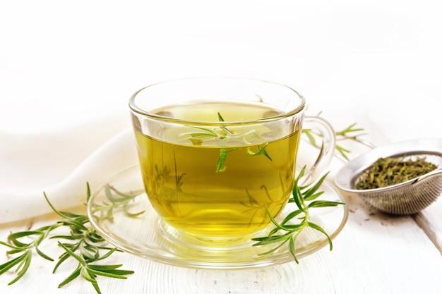 Chá de ervas de alecrim em uma xícara, uma peneira com ervas secas e guardanapo de linho sobre um fundo de placa de madeira
