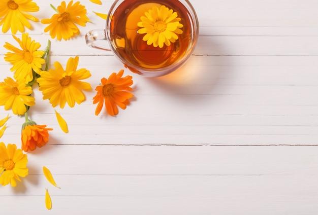 Chá de ervas de calêndula (calêndula) na mesa de madeira branca
