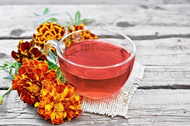 Chá de ervas de calêndula em uma xícara de vidro, flores frescas em um guardanapo de serapilheira em uma velha placa de madeira