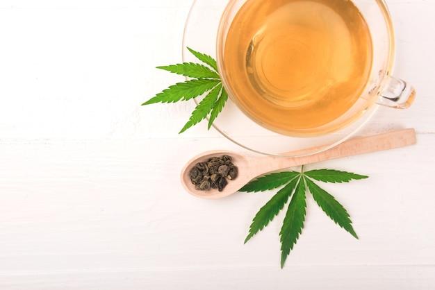 Chá de ervas de cannabis e folhas verdes de maconha em fundo branco.