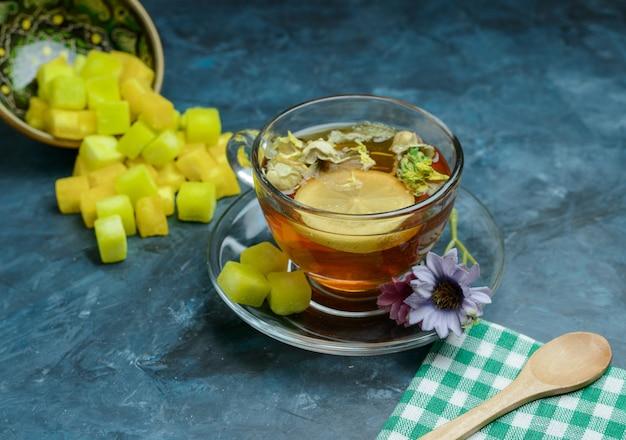 Chá de ervas de limão com cubos de açúcar, colher, toalha de chá em um copo na superfície azul escura, vista de alto ângulo.