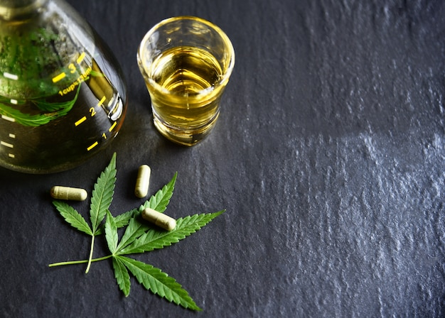 Chá de ervas de maconha folha planta cannabis e cápsula em fundo escuro