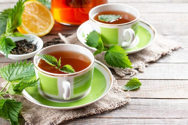 Chá de ervas de urtiga em duas xícaras na mesa de madeira