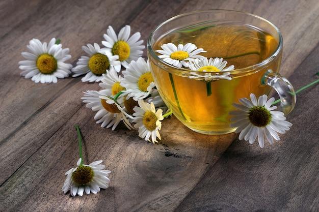 Chá de ervas de verão. xícara de chá de camomila e flores de camomila em uma mesa de madeira