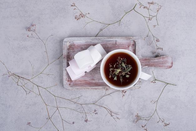 Chá de ervas e prato de marshmallows em fundo cinza. foto de alta qualidade