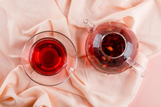 Chá de ervas em caneca de vidro e bule em rosa e têxteis.